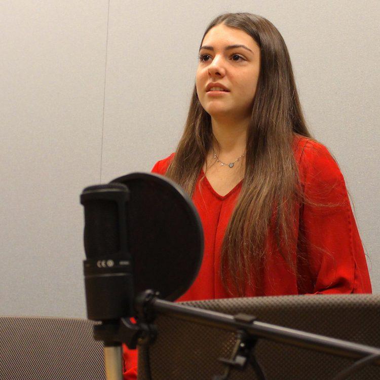 Sari Kaufman standing at microphone