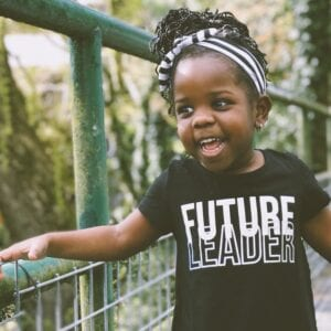 "little girl smiling, wearing shirt that says ""futuyre leader"""