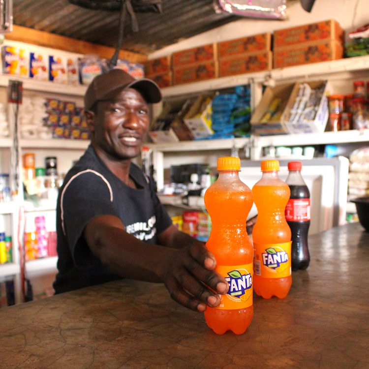 Man pushed cold drinks towards camera. he is standing in small shop in Zambia