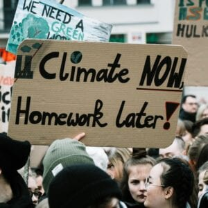 young people holding protest sign: climate now, homework later!